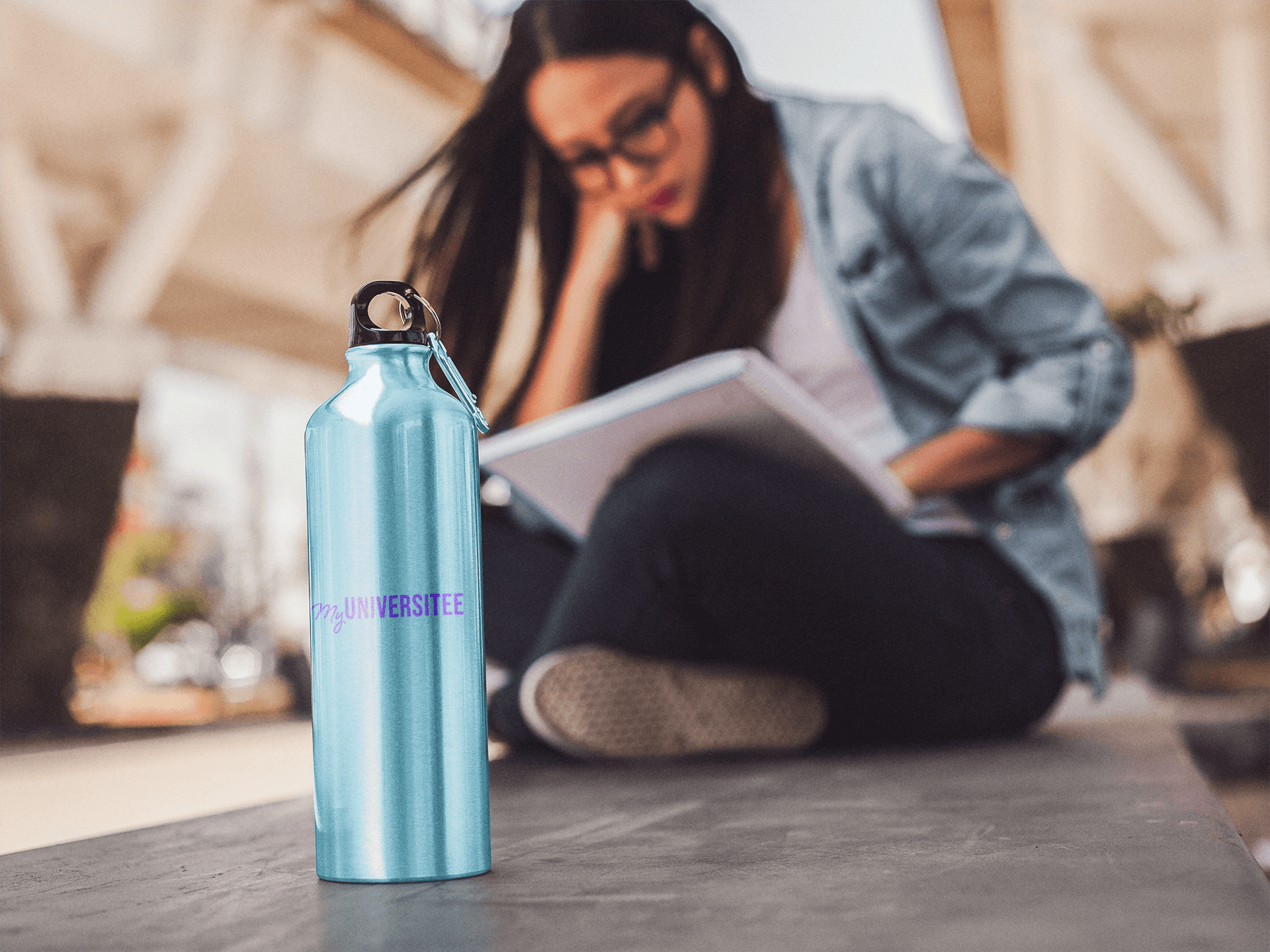 girl-sitting-down-reading-with-an-aluminum-water-mockup-bottle-near-her-a14886