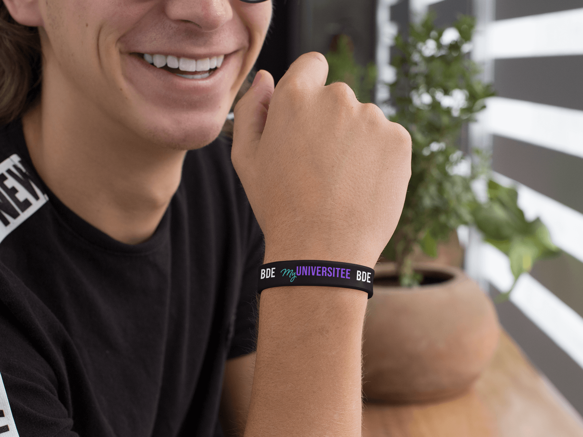 silicone-wristband-mockup-featuring-a-smiling-guy-by-a-plant-pot-28244-2